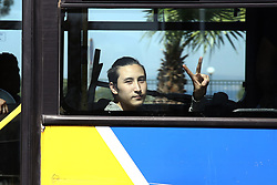 June 1, 2017 - Athens, Attica, Greece - A man from inside a bus flashes the victory sign during the evacuation of the refugee camp of the former Hellinikon Athens airport, on June 2, 2017. More than 500 hundred migrants and refugees, mainly Afghans, were housed at the camp, while more than 60.000 are stranded in Greece. (Credit Image: © Panayotis Tzamaros/NurPhoto via ZUMA Press)