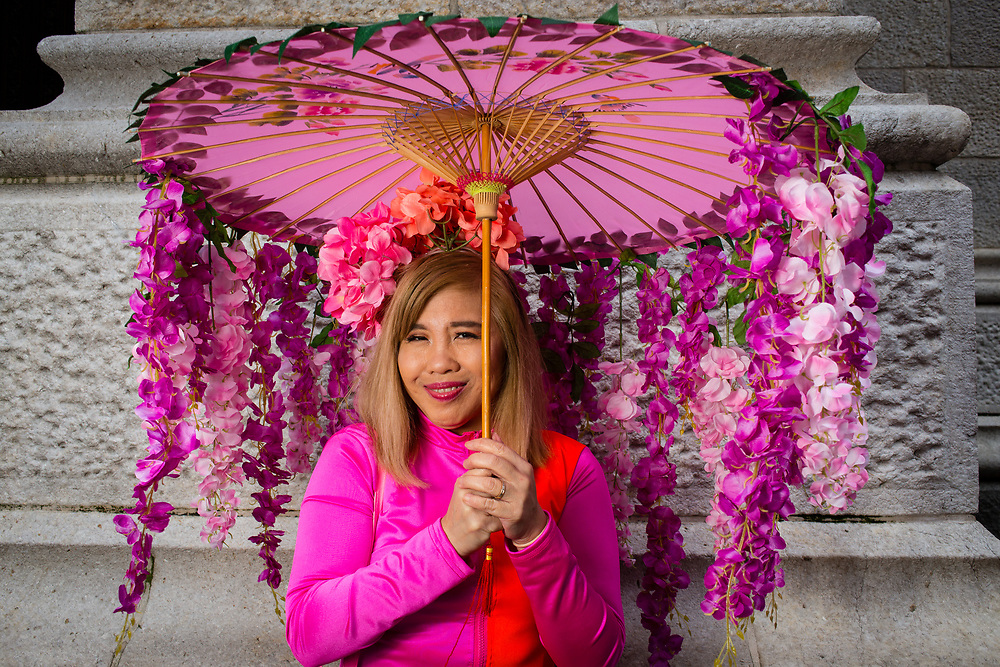 New York, NY - 21 April 2019. A woan with a parasol trimmed with flowers at the Easter Bonnet Parade and Festival on New York's Fifth Avenue.