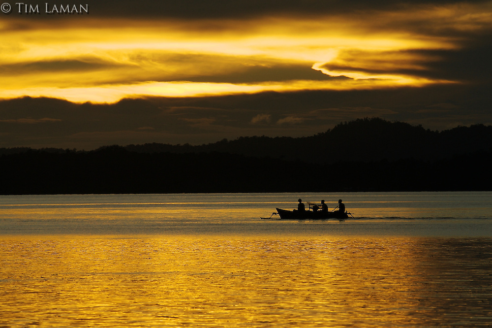 A canoe passes Gam island at sunset.