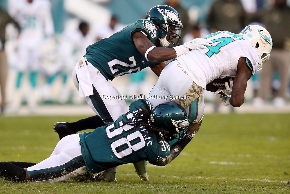 Miami Dolphins wide receiver Jarvis Landry (14) catches a late fourth quarter pass on a third down play that is good for a first down at the Dolphins 37 yard line while getting gang tackled by Philadelphia Eagles defensive back E.J. Biggers (38) and Philadelphia Eagles strong safety Walter Thurmond (26) during the 2015 week 10 regular season NFL football game against the Philadelphia Eagles on Sunday, Nov. 15, 2015 in Philadelphia. The Dolphins won the game 20-19. (©Paul Anthony Spinelli)
