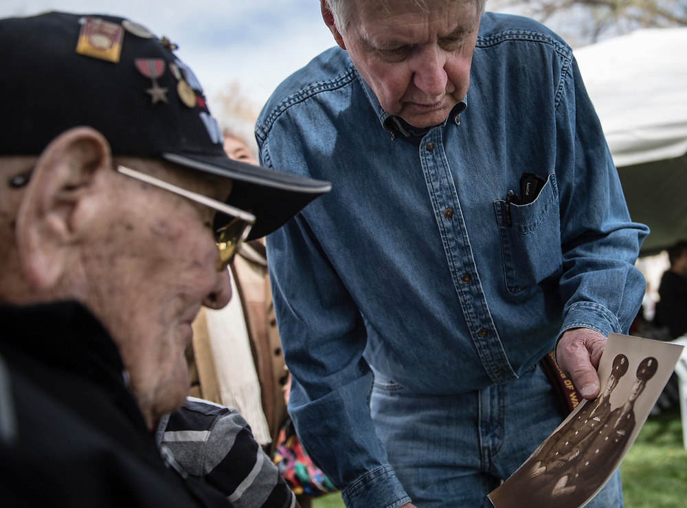 rer040817a/A1/04.08.2017/Roberto E. Rosales <br /> Trinidad Martinez(Cq),left, a Bataan survivor looks at a photo handed to him by Gary Finley containing both his father Jack Finley and grandfather Jess Finley(Cq)who both served in Battaan.  On Saturday the 75th Anniversary surrender of Bataan ceremony took place at Battan Memorial Park. <br /> Albuquerque, New Mexico(Roberto E. Rosales/Albuquerque Journal)