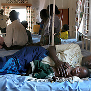 July, 15, 2006 - An HIV positive baby receiving ARV's, and whose health is improving, rests with her mother at the district hospital in Rwinkwavu, Rwanda, which the Clinton Foundation renovated in partnership with Dr. Paul Farmer's Partners in Health. Photo by Evelyn Hockstein