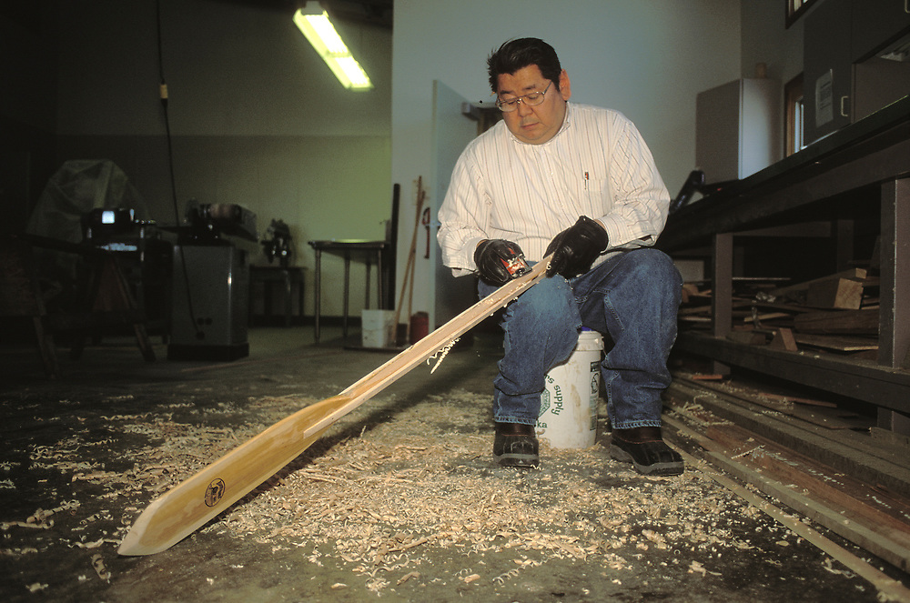 Barrow, Alaska, A native Alaskan man fine crafts a wooden paddle for a traditional umiak in his workshop.
