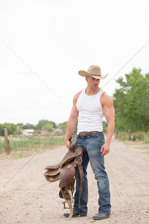 hot cowboy holding a saddle