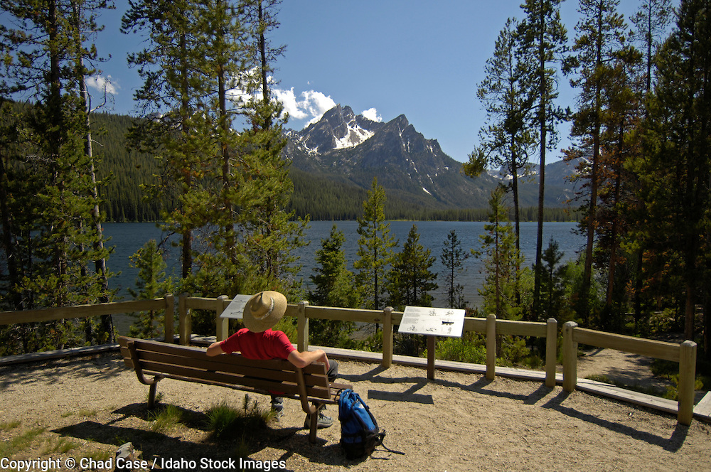 Idaho. Sawtooth National Recreation Area. Hiker rests on bench at Stanley Lake with mountains beyond. MR
