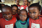 Children at the neighborhood daycare in Soweto, South Africa with traces of breakfast on their faces: pap (corn meal mixed with water). Published in Material World, page 24. This is the daycare center where Simon's son George and nephew Mateo attend while their parents are at work. The Qampie family lives in a 400 square foot concrete block duplex house in the sprawling area of Southwest Township (called Soweto), outside Johannesburg (Joberg) South Africa.