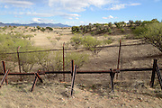 A metal wall defines the Mexican border at Sonora, Mexico, as seen from Lochiel, Arizona, USA. A large gap runs under the fence in the rural outlying area.