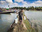 07 NOVEMBER 2014 - SITTWE, RAKHINE, MYANMAR: A man carries drinking water to fishing boats tied up in the port of a Rohingya IDP camp near Sittwe. The government of Myanmar has forced more than 140,000 Rohingya Muslims who used to live in Sittwe, Myanmar, into squalid Internal Displaced Person (IDP) camps. The forced relocation took place in 2012 after sectarian violence devastated Rohingya communities in Sittwe and left hundreds dead. None of the camps have electricity and some have been denied access to regular rations for nine months. Conditions for the Rohingya in the camps have fueled an exodus of Rohingya refugees to Malaysia and Thailand. Tens of thousands have put to sea in rickety boats hoping to land in Malaysia but sometimes landing in Thailand. The exodus has fueled the boat building boom on the waterfront near the camps. Authorities expect the pace of refugees fleeing Myanmar to accelerate during the cool season, December through February, when there are fewer storms in the Andaman Sea and Bay of Bengal.   PHOTO BY JACK KURTZ