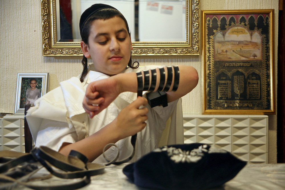 "A young Orthodox Jewish boys preparing to pray by wrapping the leather strap of his Tefillin around his arm and a Tallit (prayer shawl) around his shoulders.  The arm-Tefillin, is worn on the upper arm, while the head-Tefillin, is placed above the forehead. They serve as a ""sign"" and ""remembrance"" that God brought the children of Israel out of Egypt. According to Jewish Law, they should be worn during weekday Morning Prayer services."