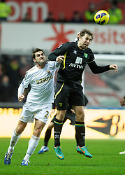 SWANSEA, WALES - Saturday, December 8, 2012: Swansea City's Angel Rangel in action against Norwich City's captain Grant Holt during the Premiership match at the Liberty Stadium. (Pic by David Rawcliffe/Propaganda)