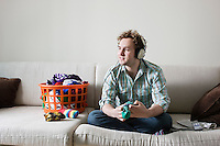 Man folding socks wearing headphones sitting on sofa
