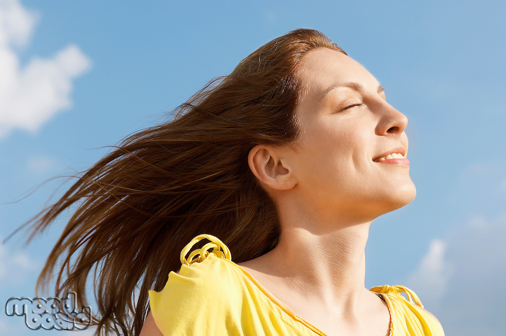 Young woman outdoors enjoying wind on face close up