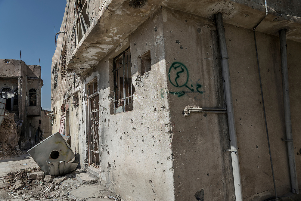 A green sign is seen painted on the walls of houses, meaning 'done' in Arabic. During ISIS occupation, militants would raid homes in search of televisions and any communication devices, confiscating them in order to prevent people from being connected to the outside world. After they had completed the raid they would paint the sign on the outside wall of each home.