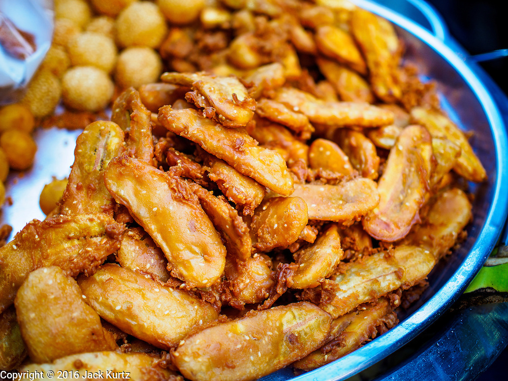 "12 JANUARY 2016 - BANGKOK, THAILAND: Fried banana fritters, a popular Thai street food snack, for sale in Khlong Toey Market in Bangkok. Khlong Toey (also called Khlong Toei) Market is one of the largest ""wet markets"" in Thailand. The market is located in the midst of one of Bangkok's largest slum areas and close to the city's original deep water port. Thousands of people live in the neighboring slum area. Thousands more shop in the sprawling market for fresh fruits and vegetables as well meat, fish and poultry.         PHOTO BY JACK KURTZ"