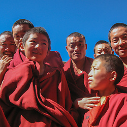 Boeddhist monks standing in a crowd at the front of their monastery, Central TIbet.