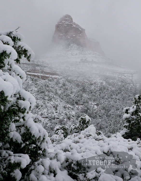 Photo by Gary Cosby Jr.  ..A Spring snowstorm blankets the Sedona area in white covering the fabled red rocks with a layer of white.  Scenic Highway 89A winds its way through the snow covered hillsides providing spectacular views.
