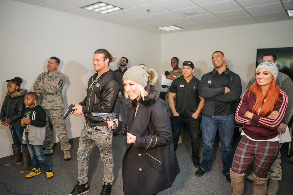 Prince George's County, MD - December  13, 2016:  WWE Superstars Dolph Ziggler, left, and Renee Young, right, use weapons fitted with lasers to compete in a hostage simulation video during Tribute to the Troops Day at the Joint Base Andrews in Prince George's County, Maryland.  WWE Superstars will spend time with members of all five branches of the military.  WWE began Tribute to the Troops in 2003 as a way to honor our servicemen and women and their families.   (Greg Kahn for ESPN)