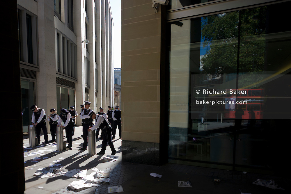 Metropolitan police officers guard the Stock Exchange premises at Newgate Street, Paternoster Square in the City of London during world corporate greed and government austerity measures protests.