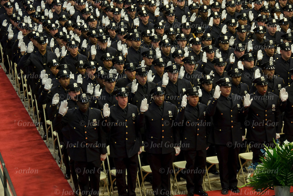 Right hand raised taking the &quot;Oath of Office&quot; at the New York City Police Academy Graduation Ceremony on June 28, 2012 at St.John's University in Queens NY.  <br />