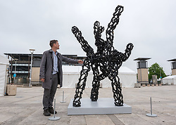 """© Licensed to London News Pictures. 08/06/2018. Bristol, UK. Bristol artist LUKE JERRAM stands by his new sculpture """"Inhale"""", his newest piece which is unveiled this week for Bristol's Festival of Nature. Jerram's Inhale sculpture is designed to make the damaging effects of air pollution visible to everyone. It is three metres high and represents a diesel soot particle, actual size one micron but magnified 3 million times. The sculpture is made out of coal, with pyrite and calcite representing larger particles such as from vehicle disc brakes, and tiny bits of glitter representing tiny chemicals in diesel soot, some of which are thought to be carcinogenic. Jerram said the inspiration for the piece came from the recent Volkswagen diesel scandal and a friend whose child suffers from asthma. He chose diesel soot as the focus of the artwork as diesel vehicles are a significant contributor towards air pollution in the UK and in Bristol, air pollution is thought to contribute to five deaths a week. The sculpture is making its first public appearance as part of the Festival of Nature in Bristol on the weekend of June 9-10, and has been commissioned by the University of the West of England as part of its Our City Our Health project, which aims to draw attention to the health impacts of poorly designed cities. Photo credit: Simon Chapman/LNP"""