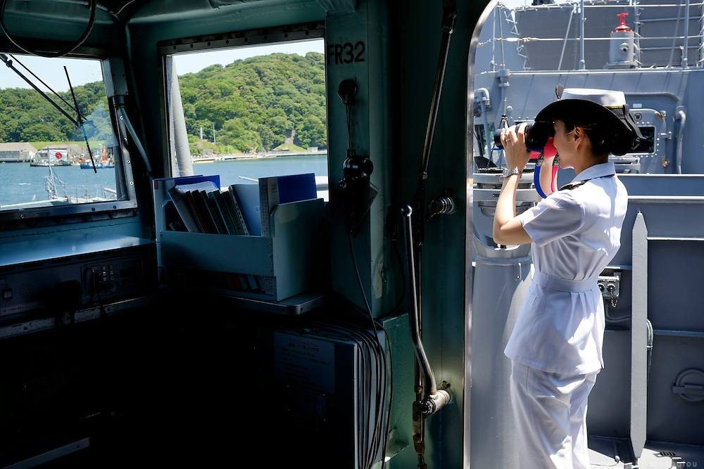 Miho Ootani, the first woman destroyer captain of Japan's Marine Self Defence Forces (MSDF), on board the Yamagiri in Yokosuka army base near Tokyo. While performing her duties, she always checkes what is ahead with her binoculars. Here in the outdoors space of the bridge.