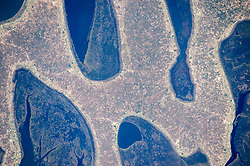 An astronaut aboard the International Space Station took this photograph of the strange rounded shapes along the coastline of Zambia's Chilubi Island. The light-toned sand island stands out from the dark waters of Lake Bangweulu.<br /> In the photo we see a few patches of open water between the fingers of the island. The waters are crowded by areas of aquatic vegetation and wetland (reeds, papyrus, and floating grass) in green. Lake Bangweulu, which is only 4 meters (13 feet) deep on average, is rich enough to supply fish for the copper-mining towns to the west.<br /> Chilubi Island has 100 kilometers (60 miles) of coastline, providing prime access to the richest fishing waters in northern Zambia. Those coastlines are smoothed by easterly winds that erode ancient sand dunes. The narrow strips of lighter toned land along the shorelines are areas that have been mostly denuded of vegetation by residents of the densely populated fishing villages.<br /> The explorer and missionary David Livingstone was the first European to visit the lake (1868).<br /> Astronaut photograph ISS044-E-00661 was acquired on June 14, 2015, with a Nikon D4 digital camera using an 1150 millimeter lens, and is provided by the ISS Crew Earth Observations Facility and the Earth Science and Remote Sensing Unit, Johnson Space Center. The image was taken by a member of the Expedition 44 crew. The image has been cropped and enhanced to improve contrast, and lens artifacts have been removed. The International Space Station Program supports the laboratory as part of the ISS National Lab to help astronauts take pictures of Earth that will be of the greatest value to scientists and the public, and to make those images freely available on the Internet. Additional images taken by astronauts and cosmonauts can be viewed at the NASA/JSC Gateway to Astronaut Photography of Earth. Caption by M. Justin Wilkinson, Texas State University, Jacobs Contract at NASA-JSC.<br />  *** Please Use Credit from Credit Field ***