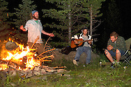 Will Wilson, Carlos Vargas and Gus Grant camp alongside upper Flat Creek on Saturday night, passing the time with campfire music and stories of how cold it was to swim in the headwaters of the waterway that meanders through Jackson.