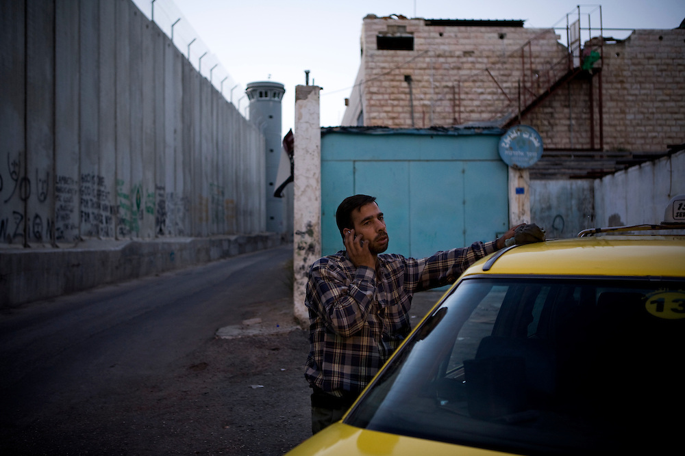 A Palestinian man talks on the phone next to his taxi under the shadow of an Israeli watchtower and a section of the security wall, Bethlehem. 14th May 2008