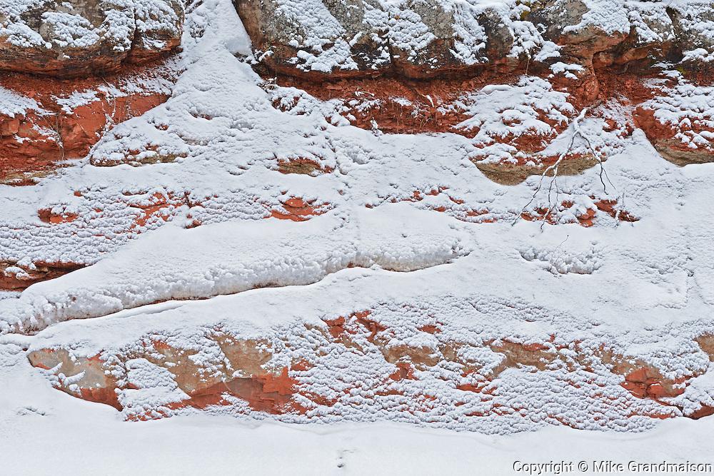 Red rock with falling snow<br /> <br /> Nipigon<br /> Ontario<br /> Canada