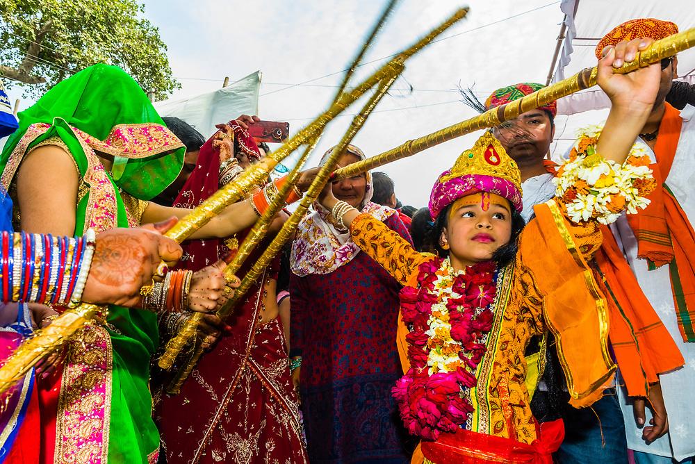 Girl dressed as Radha (Hindu goddess; lover and companion of Hindu God, Krishna) plays Lathmar Holi with sticks, Chhadi Mar Holi (local Holi (festival of colors); village of Gokul, near Mathura, Uttar Pradesh, India.