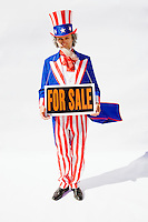 "Uncle Sam on White Background holding a ""For Sale"" sign strung around his neck...Model Release: 20080813_MR_A"