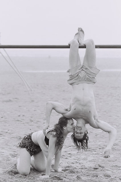 woman kissing a man hanging upside down on a bar at the beach