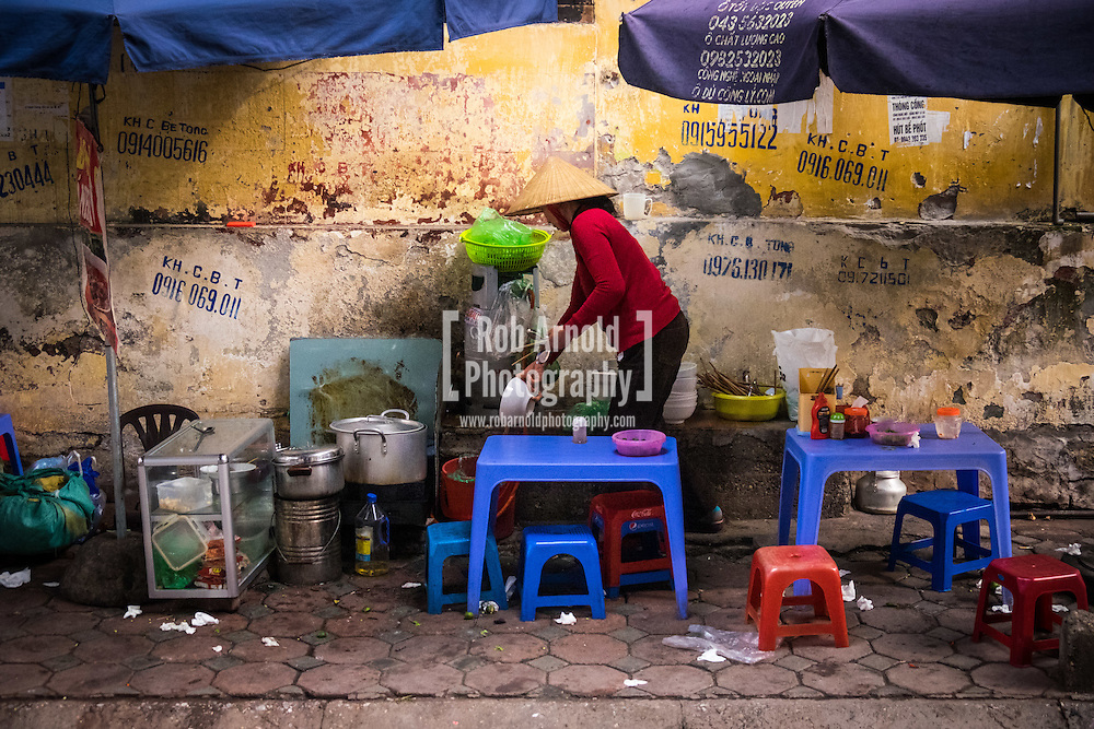 A woman selling Pho noodle soup from her pavement stall in Hanoi