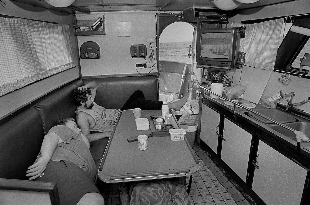 PZ 198, the 'Aaltje Adriaantje'.<br /> Richard and Malcolm watching television in the galley.<br /> <br /> These boats are out for seven days at a time in all weathers and the nets are hauled up every three hours around the clock. The crew consists of five self-employed fishermen who share the profits of the catch.