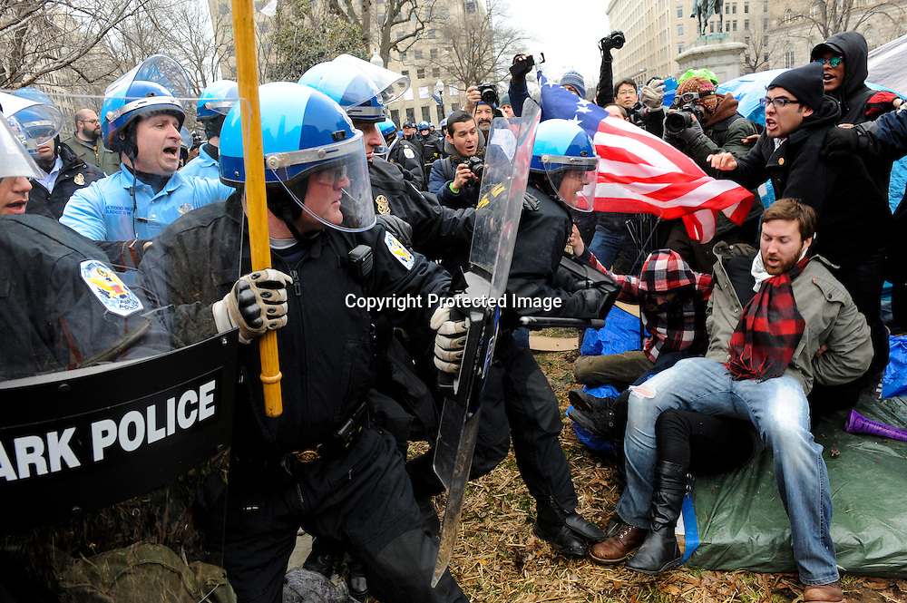 U.S. National Park Service police push aside protestors as they cordon-off the Occupy DC encampment in McPherson Square in Washington. Police officers wearing helmets and carrying shields arrived at the site where protesters with the Occupy movement have been staging a demonstration since October, but it was not immediately clear whether they would evict the protesters.