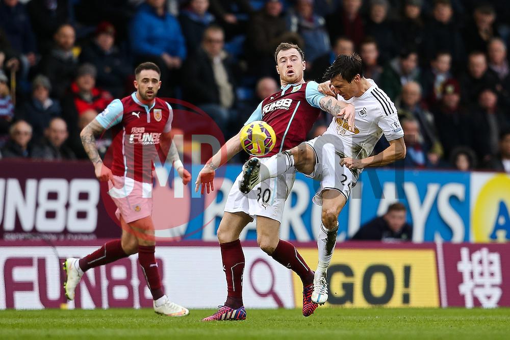 Jack Cork of Swansea City challenges Burnley's Ashley Barnes  - Photo mandatory by-line: Matt McNulty/JMP - Mobile: 07966 386802 - 28/02/2015 - SPORT - Football - Burnley - Turf Moor - Burnley v Swansea City - Barclays Premier League