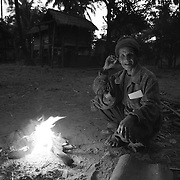 """An elderly man sits by a fire in the """"bomb village"""" of Ban Senphen. The village is located in the Ban Phanhop valley, one of the """"chokes"""", or narrow corridors along the Ho Chi Minh Trail in Laos that were heavily bombed by American forces during the Vietnam War. Much of the village infrastructure, from housing supports to boats, are constructed from the metal from downed airplanes and unexploded bombs."""