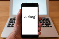 Using iPhone smartphone to display logo of Vueling, Spanish low-cost airline