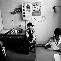 """DONGLU, 11 MARCH 2001: a nun writes a diagnoses for a patient while his father looks on in an """"emergency """" station near the official catholic church in Donglu.China cut relations with the Vatican in the early fifites and since then, established a Patriotic catholic Church that's controlled by Chinese authorities.<br />Catholics who refused to give up their ties with the Vatican, started worshipping in underground churches and consequently were persecuted for a long time. Since the late nineties though, relations with the Vatican informally started to improve. Although China still has no diplomatic relations, many representatives from official churches met the pope John Paull II secretely . The Vatican, under the pope's leadership, has made several efforts to recover the tie with China. In February 2006 , Hong Kong Bishop Joseph Zen was named one of the first 15 new cardinals, which is seen by many as a gesture of goodwill and a significant step towards recovering the Vatican-China relationship."""