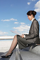 Businesswoman sitting outdoor steps reading newspaper profile