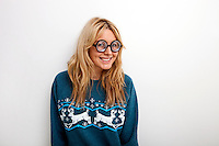 Portrait of happy woman in sweater wearing eyeglasses against white background