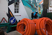 Coils of plastic cable casings and roadworks signs all tidied away behind fencing in a south London side street, Southwark.