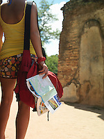 Young woman looking at ancient ruins holding guide book back view mid section