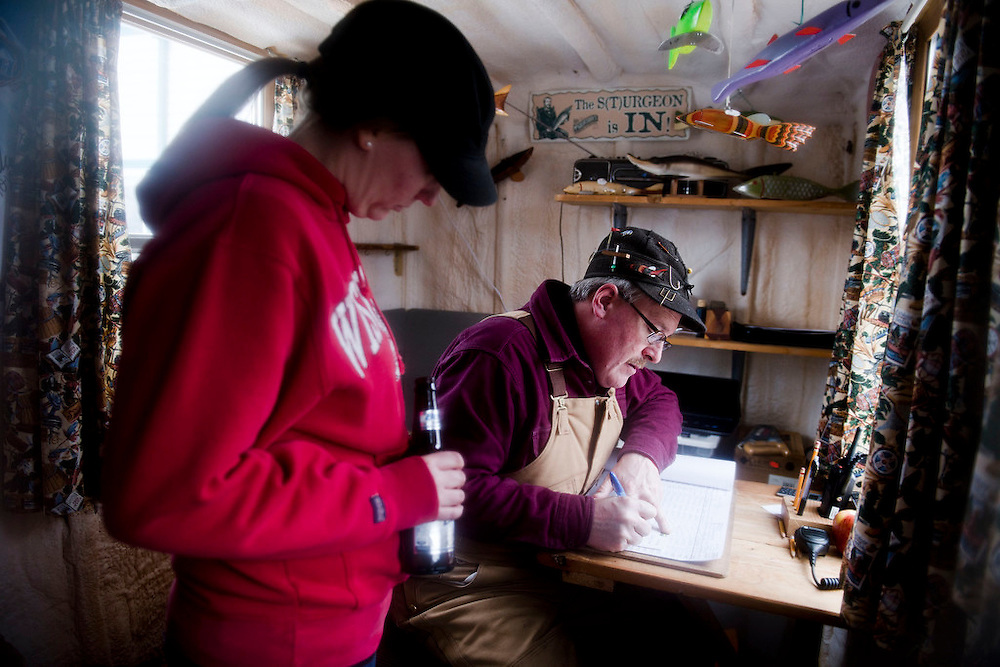 STOCKBRIDGE, WI -FEB. 16, 2015: Kendall Kamke, 56, the Senior Fisheries Biologist, writes down data gathered from a sturgeon speared by Cassie Stumpf, 29, left, at the Stockbridge registration station. Spear fishermen bring in their catch of the day to the registration station at Harbor Bar in Stockbridge, WI to weigh and measure the sturgeon Monday, Feb. 16, 2015. 13,000 licenses were sold for the 2015 sturgeon spearing season, and 233 fish were caught Monday between all of the registration stations, with 62 being registered in Stockbridge. The season started Feb. 14, 2015 and lasted until Feb. 21, 2015 on Lake Winnebago with a total of 1870 sturgeon speared. The average success rate for spearers is 10-12% and some people go years without spotting anything from their shanty. Lauren Justice for The New York Times