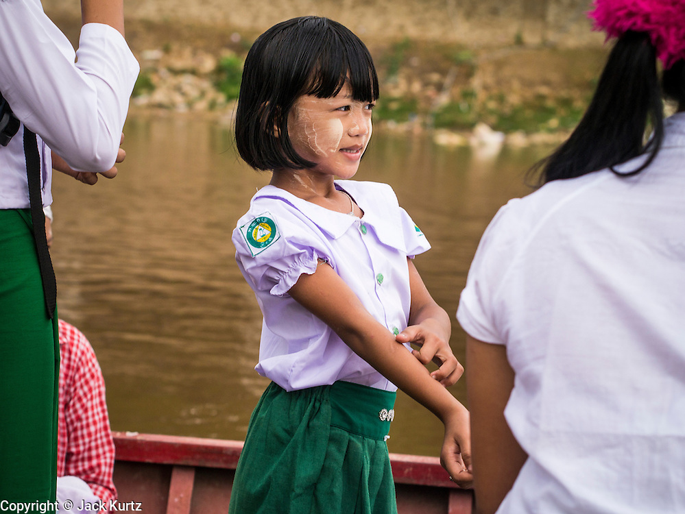 23 MAY 2013 - MAE SOT, TAK, THAILAND: A Burmese girl in a boat goes back to Myawaddy, Myanmar from Mae Sot, Thailand. Fifty years of political turmoil in Burma (Myanmar) has led millions of Burmese to leave their country. Many have settled in neighboring Thailand. Mae Sot, on the Mae Nam Moei (Moei River) is the center of the Burmese emigre community in central western Thailand. There are hundreds of thousands of Burmese refugees and migrants in the area. Many live a shadowy existence without papers and without recourse if they cross Thai authorities. The Burmese have their own schools and hospitals (with funding provided by NGOs). Burmese restaurants and tea houses are common in the area.    PHOTO BY JACK KURTZ