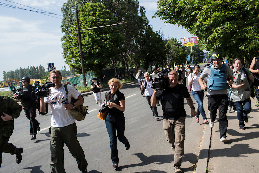 DONETSK, UKRAINE - MAY 26: Journalists run from fighting outside the Donetsk airport, scene of an hours-long battle between pro-Russian separatists and Ukrainian forces, on May 26, 2014 in Donetsk Ukraine. A day after businessman Petro Poroshenko won Ukraine's presidential election, separatists occupied the airport, leading to a military response. (Photo by Brendan Hoffman/Getty Images)