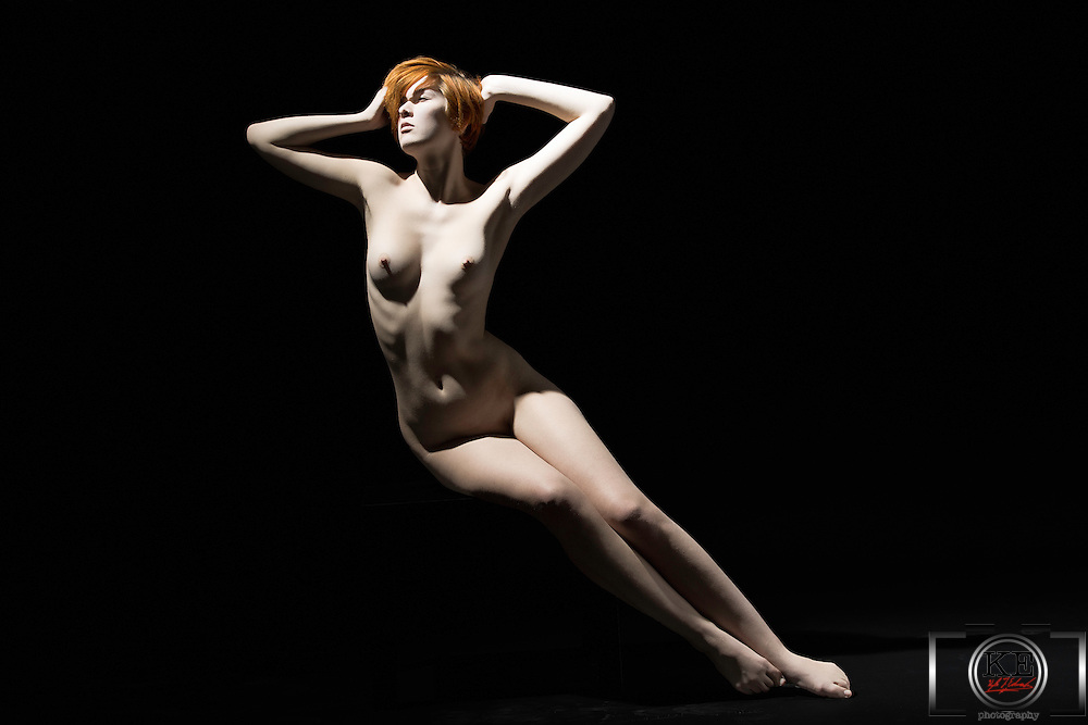 A nude lady, stretched out in blackness.