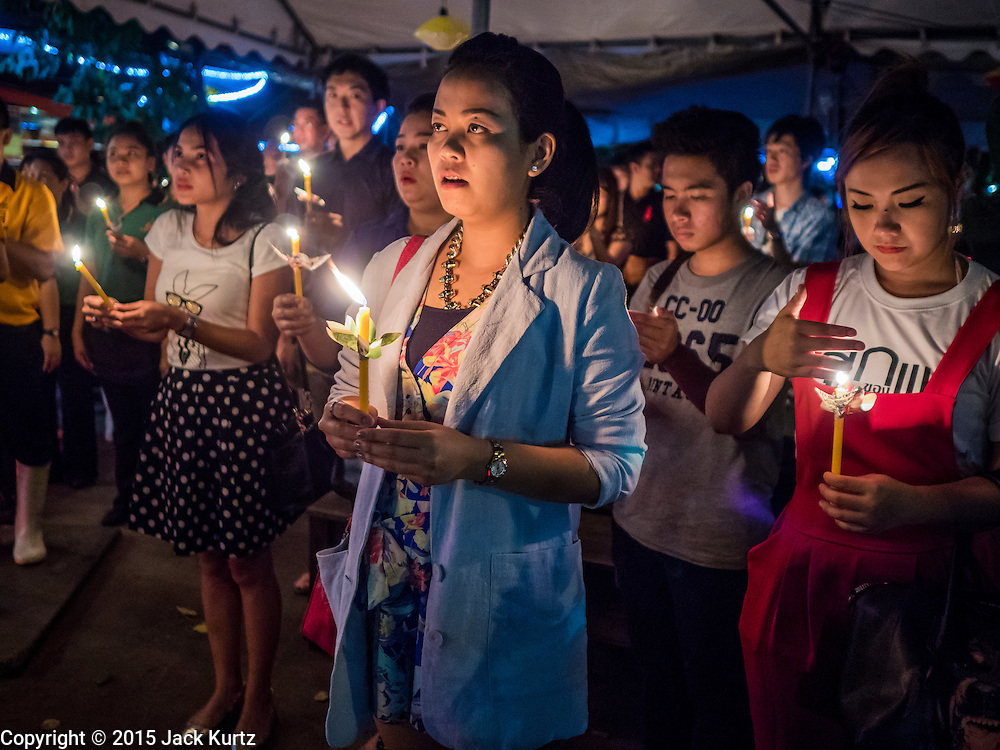 12 AUGUST 2015 - BANGKOK, THAILAND:  Patrons in a Bangkok restaurant hold lit candles to honor Queen Sirikit of Thailand on the Queen's 83rd birthday. Queen Sirikit was born Mom Rajawongse Sirikit Kitiyakara on August 12, 1932. She is the queen consort of Bhumibol Adulyadej, King (Rama IX) of Thailand. She met Bhumibol in Paris, where her father was the Thai ambassador. They married in 1950, she was appointed Queen Regent in 1956. The King and Queen had one son and three daughters. She has not made any public appearances since her hospitalization in 2012. Her birthday is celebrated as Mother's Day in Thailand, schools and temples across Thailand hold ceremonies to honor the Queen and mothers.    PHOTO BY JACK KURTZ