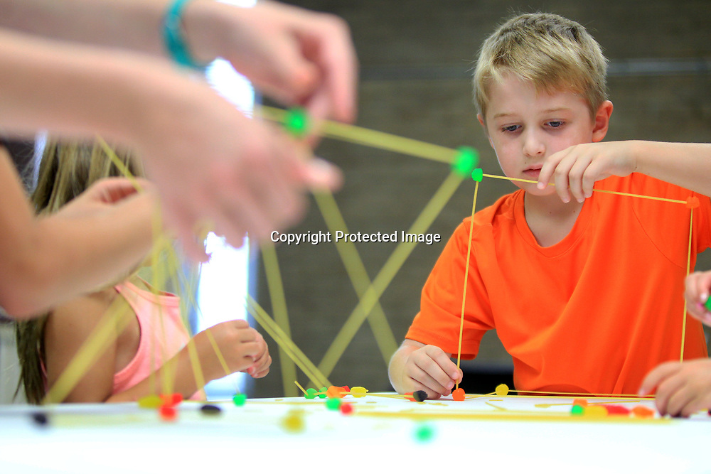 Kaleb Irby, 6, of Saltillo, uses spaghetti and gummy candy to construct a set of cubes so they will stand on their own during a engineering day project at the Lee County Library in Tupelo Tuesday afternoon.