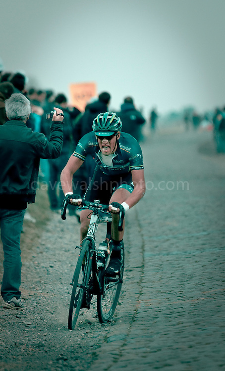 French cyclist Damien Gaudin, Team Europcar jumps off the cobblestones onto gravel, 13km from the finish of the 2012 Paris Roubaix professional cycling race classic. Here, Gaudin is passing Gruson, the 3rd last section of cobbles, 243km into the 256.5km route from Compiègne, near Paris, to Roubaix, northern France, which crosses 51.5km of pavé - 27 sections of ancient cobblestones, along the way. Gaudin placed 25th, out of 86 finishers out of 196 starters.